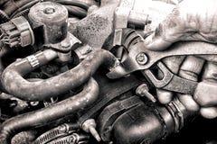Mão do mecânico do auto reparo que repara uma peça do motor de automóveis Fotografia de Stock