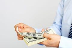 A mão dos homens que guarda notas de dólar do americano cem do dinheiro Mão do dinheiro de oferecimento do homem de negócio Imagem de Stock Royalty Free