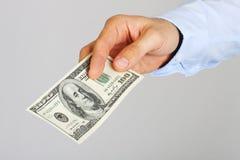 A mão dos homens que guarda notas de dólar do americano cem do dinheiro Mão do dinheiro de oferecimento do homem de negócio Fotografia de Stock