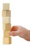 A mão estabelece um cubo de madeira. Fotos de Stock Royalty Free