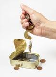 A mão fêmea derrama abaixo das moedas em peixes pode Fotografia de Stock Royalty Free