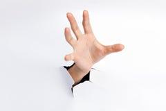 Mão fêmea que alcança através da folha de papel rasgada Fotografia de Stock Royalty Free
