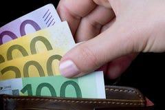 Mão fêmea que guardara o dinheiro Fotos de Stock Royalty Free