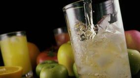 Mo lento O suco de maçã derrama em um vidro com gelo em um fundo preto video estoque