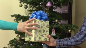 A mão masculina do homem dá a caixa de presente atual com a fita para a mulher fêmea filme