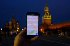 Mão masculina que guarda um smartphone com corrida de Google Maps app Fotografia de Stock Royalty Free