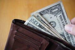 Mão masculina que guarda uma carteira de couro e que retira a moeda americana (dólares americanos de USD,) Fotos de Stock Royalty Free