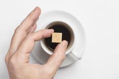 Mão masculina que mantém o cubo do açúcar de bastão sobre o copo do café preto contra a opinião superior do fundo branco com espa Imagens de Stock Royalty Free