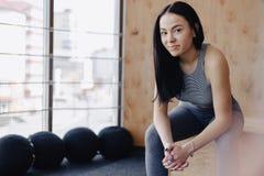Mo?a no sportswear em um gym em um fundo simples, em um tema da aptid?o, em um crossfit e no esporte imagem de stock
