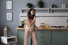 Mo?a nos pijamas que dan?am na manh? na cozinha fotografia de stock