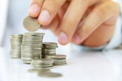 A mão pôr a moeda à pilha Fotos de Stock Royalty Free
