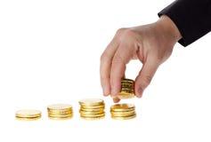 A mão pôs moedas na pilha de moedas Fotos de Stock Royalty Free