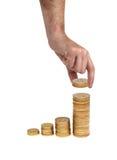 A mão põr a moeda à escadaria do dinheiro Imagem de Stock Royalty Free