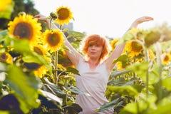 Mo?a que aprecia a natureza no campo dos girass?is no por do sol, retrato da menina redheaded bonita da mulher com girass?is foto de stock