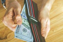 Mão que guarda a carteira preta Fotografia de Stock Royalty Free
