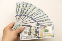 Mão que guarda cem cédulas do dólar Fotografia de Stock Royalty Free
