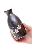 Mão que guarda a garrafa japonesa da causa Fotografia de Stock