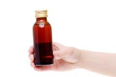 Mão que guarda a garrafa marrom da medicina Imagens de Stock Royalty Free