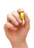 Mão que guarda o marcador amarelo Imagens de Stock