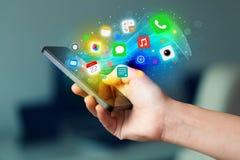 Mão que guarda o smartphone com ícones coloridos do app Fotografia de Stock