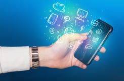 Mão que guarda o smartphone com ícones dos meios Fotografia de Stock