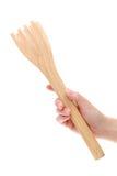 Mão que guarda tenazes de brasa de madeira da cozinha Imagem de Stock Royalty Free