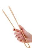 Mão que guarda tenazes de brasa de madeira da cozinha Imagens de Stock