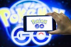 A mão que guarda um telefone celular que joga Pokemon vai jogo com fundo do borrão Imagem de Stock