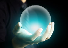 Mão que guarda uma bola de cristal de incandescência Foto de Stock
