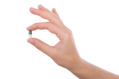 Mão que mantem uma cápsula ou um comprimido isolada Fotos de Stock Royalty Free