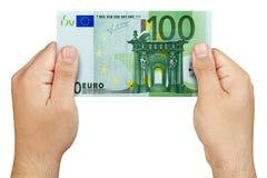 Mão que mantém a cédula do euro 100 isolada Fotos de Stock Royalty Free