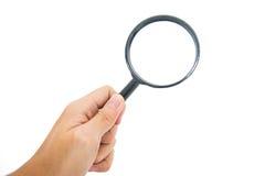 Mão que mantém a lente de aumento preta de vidro Imagem de Stock Royalty Free