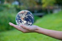 Mão que prende um globo. Excepto o ambiente da terra Fotos de Stock