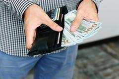 Mão que puxa 100 dólares de cédulas Imagens de Stock