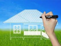 Mão que tira uma casa em uma paisagem Fotos de Stock