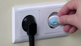 A mão remove o fio da tomada da tomada da segurança da criança da tomada e da inserção vídeos de arquivo