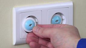 A mão retira o fio da tomada da tomada da segurança da criança da tomada e da inserção filme