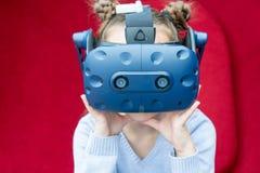 Mo?a surpreendida que experimenta a realidade virtual com uns auriculares de VR na cabe?a imagens de stock royalty free