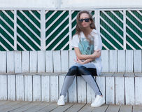 A moça bonita com cabelo longo nos óculos de sol senta-se nas etapas de madeira brancas Imagens de Stock