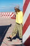 A moça bonita no moderno veste-se, óculos de sol, chapéu, steping com uma trouxa no fundo de uma parede com listras Imagens de Stock Royalty Free
