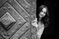 Moça bonita que espreita da porta de madeira antiga de trás Imagens de Stock Royalty Free