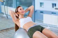 Moça bonita que faz exercícios com a bola do ajuste no gym Fotos de Stock Royalty Free