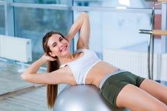 Moça bonita que faz exercícios com a bola do ajuste no gym Imagens de Stock Royalty Free