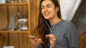 A moça com música de escuta dos fones de ouvido de um smartphone e canta em casa vídeos de arquivo