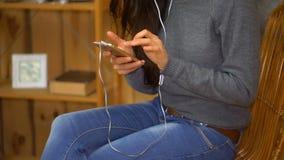 A moça com música de escuta dos fones de ouvido de um smartphone e canta em casa video estoque