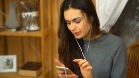 A moça com música de escuta dos fones de ouvido de um smartphone e canta em casa filme
