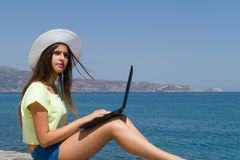 Moça com portátil, no short e no chapéu branco Foto de Stock