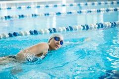 Moça nos óculos de proteção que nada o estilo do curso de rastejamento dianteiro Imagem de Stock