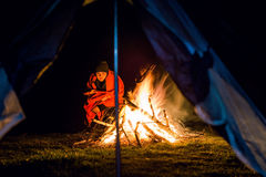Moça perto do fogo do acampamento com cobertura Fotografia de Stock