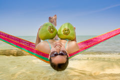 Moça que encontra-se em uma rede que guarda dois cocos Fotografia de Stock Royalty Free